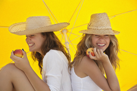 Pretty women eating fruit in the shade LANG_EVOIMAGES