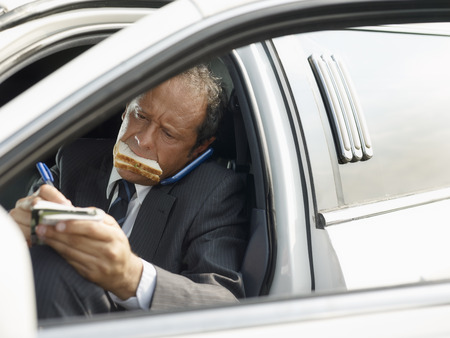 notations: Driver eating sandwich on limousine