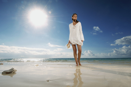 Woman walking on beach LANG_EVOIMAGES