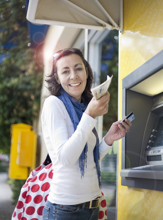 monies: Woman getting money from cash machine LANG_EVOIMAGES