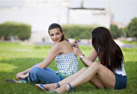 lean back: Young women writing postcard