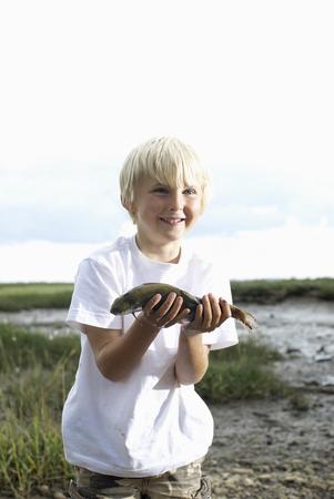Boy holding fish up LANG_EVOIMAGES