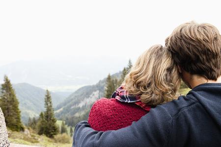 Man hugging woman watching landscape