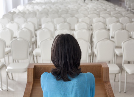 conforms: Woman standing before empty chairs LANG_EVOIMAGES