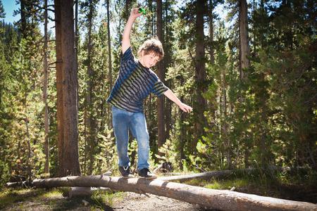 intersects: Boy walking across log