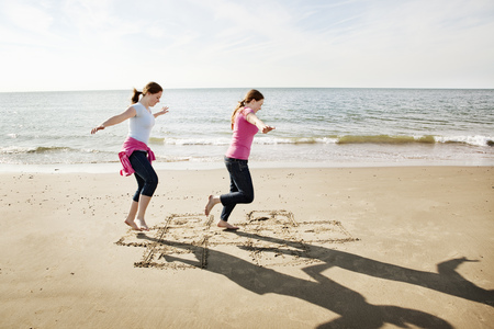 gratify: Girls playing hopscotch on beach LANG_EVOIMAGES