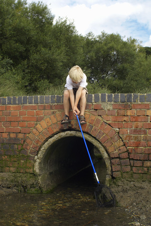 jeopardizing: Boy fishing with net from bridge