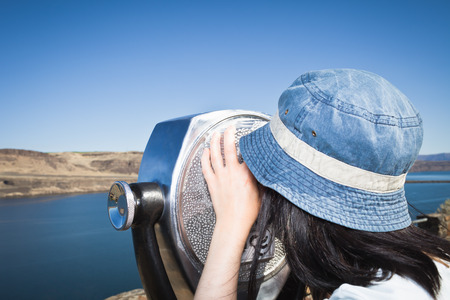 Woman using telescopic viewer LANG_EVOIMAGES