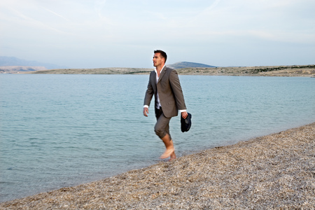 uncomplicated: Businessman walking on the beach LANG_EVOIMAGES