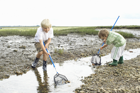 Two boys playiing in stream with nets
