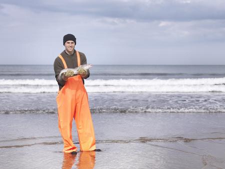 omnivore: Fisherman on shore holding fish LANG_EVOIMAGES