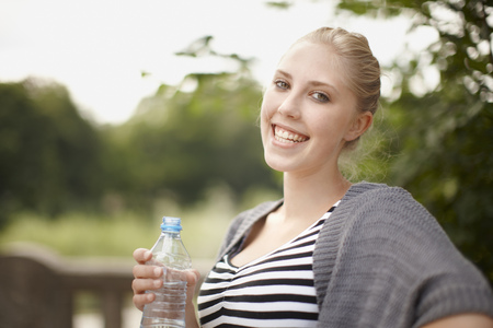 sipping: Young girl smiling at camera with water