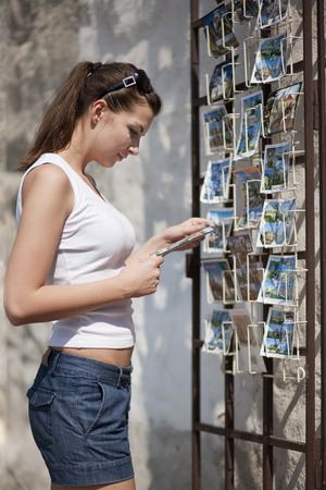 Woman looking at postcards LANG_EVOIMAGES