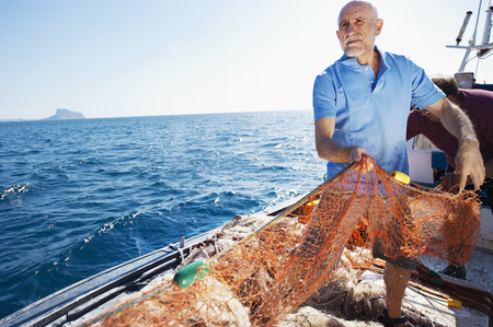 Fisherman on boat pulling in nets LANG_EVOIMAGES