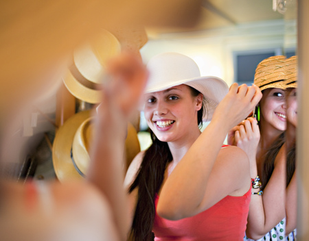 pay raise: Young women trying on hats