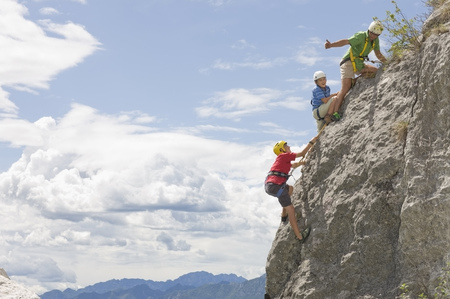 rockclimber: Man climbing rock with two boys LANG_EVOIMAGES