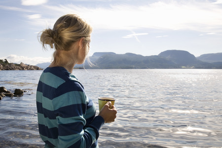 caffeine free: Woman with coffee by sea and mountains LANG_EVOIMAGES