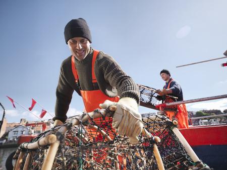 Fishermen carrying lobster pots on boat
