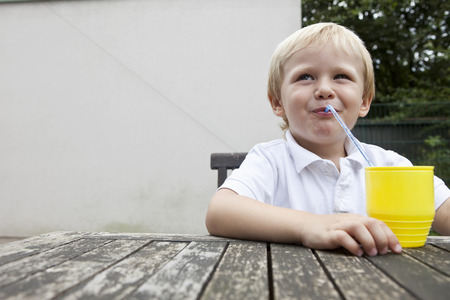 refreshed: Young Boy trinking juice with a straw
