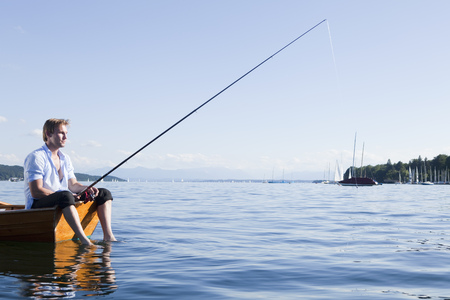 Businessman with fishing rod in rowboat LANG_EVOIMAGES