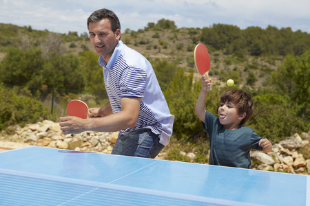 Father and son playing table tennis LANG_EVOIMAGES