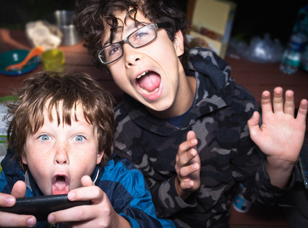 niños jugando videojuegos: Muchachos emocionados por el sistema de juego portátil