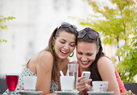 in twos: Young women looking at phone in cafÈ LANG_EVOIMAGES