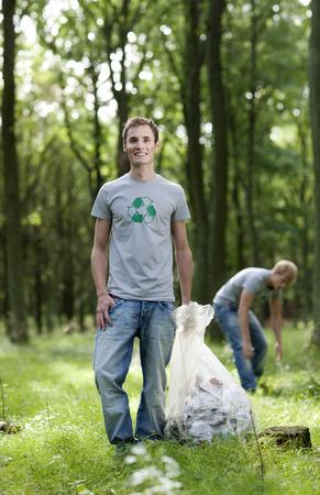 obligations: Young man holding trash bag in nature LANG_EVOIMAGES
