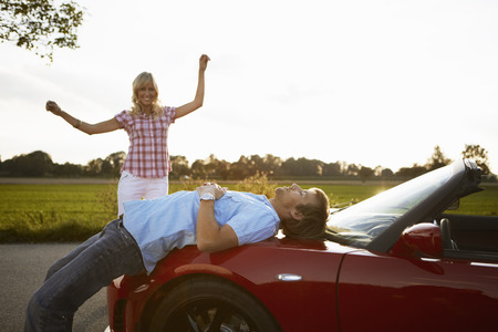 remoteness: Couple relaxing in nature around a car
