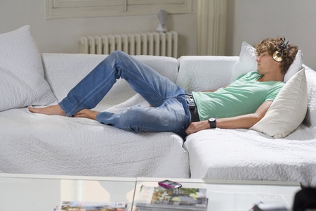 musically: Young man wears headphones relaxes couch
