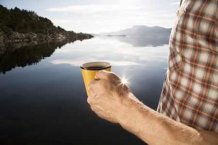 caffeine free: Man having coffee by sea and mountains