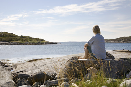 secluded: Woman sitting and looking out to sea