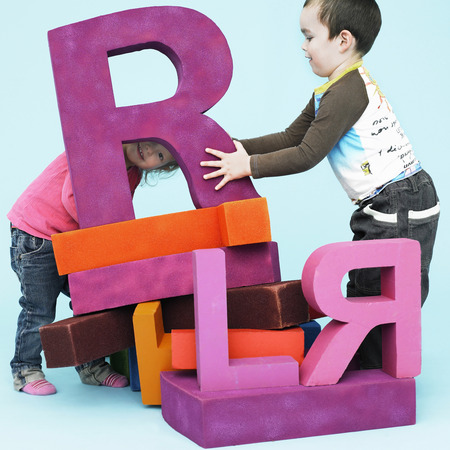 accomplishes: Toddlers playing with oversize letters