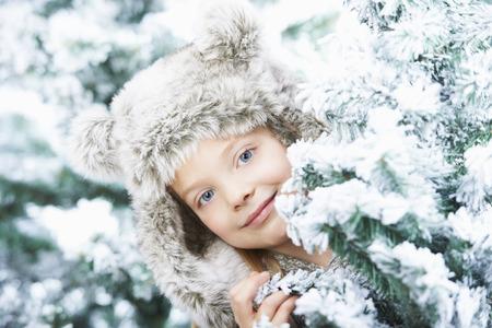 Girl standing between snowy trees