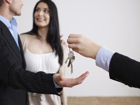 Makler übergibt Schlüssel an Paar