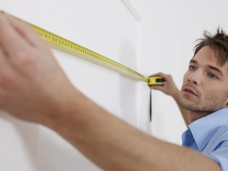 Mann hält konzentriert Maßband an Wand