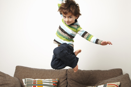 mischeif: Young boy jumping on sofa