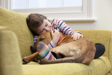 doze: Young girl cuddling her dog on the sofa