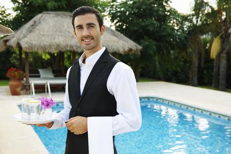 lavish: Hotel waiter holding tray by hotel pool