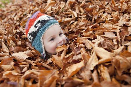 enclose: Girl buried in autumn leaves