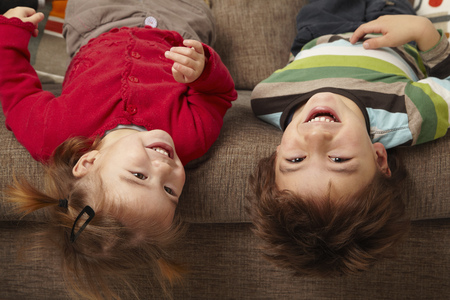 brotherly love: Young boy and girl laughing on sofa