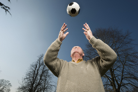 Older man playing with soccer ball
