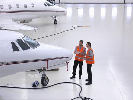 high flown: Engineers in jet aircraft hangar