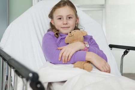 sickly: Ill girl with toy in bed,smiling LANG_EVOIMAGES