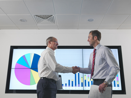 strategize: Businessmen shake hands with screen