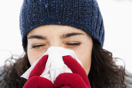 tissues: Woman wiping nose close-up