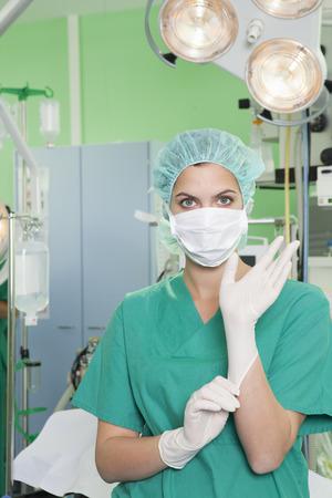 Nurse in scrubs putting on gloves