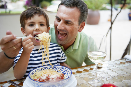 Father and son eating spaghetti LANG_EVOIMAGES