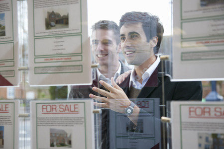 browses: Couple looking into estate agents window