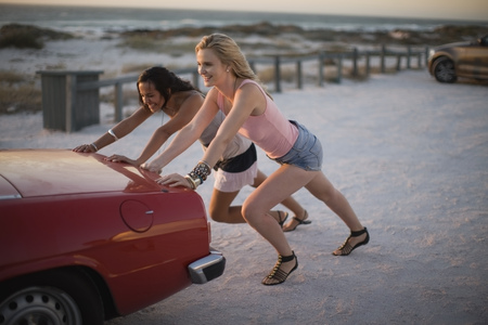 overcoming adversity: Girls pushing their broken car